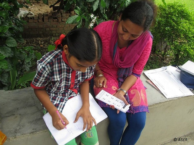 A woman conducts the ASER assessment with a young girl.