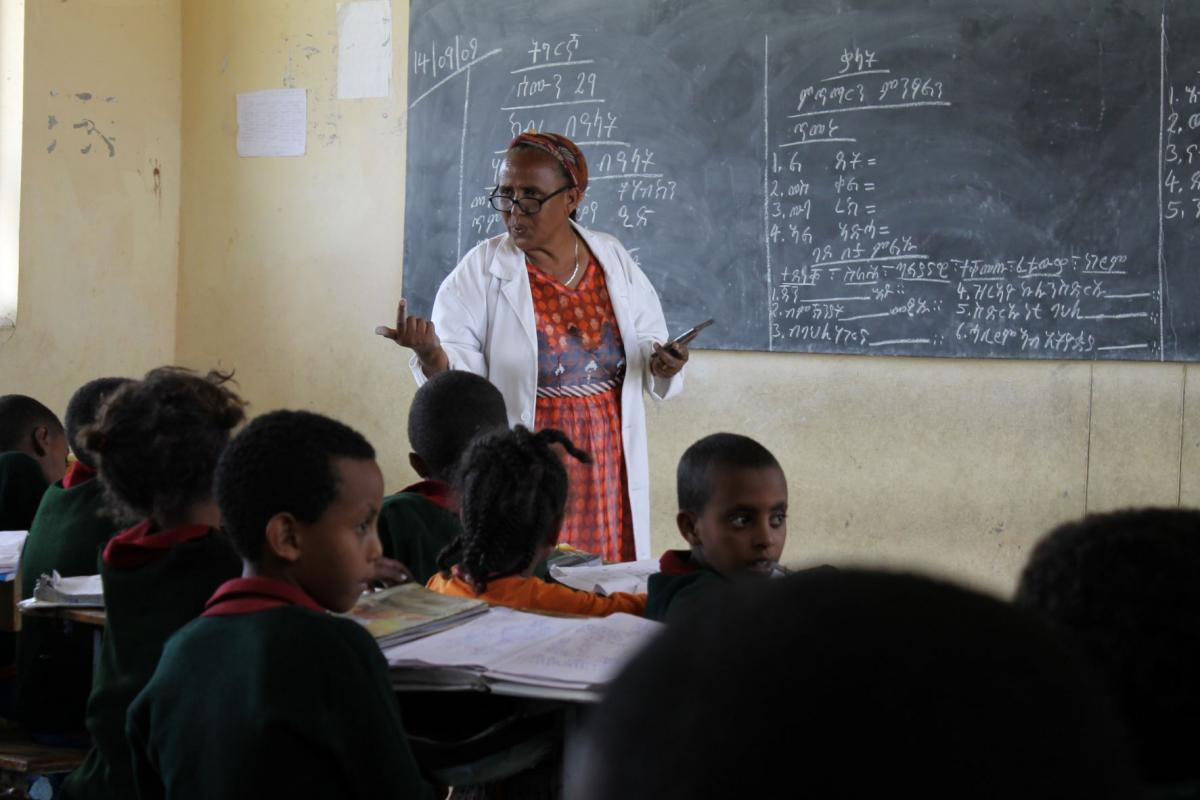 A teacher in Ethiopia stands in front of a blackboard and is delivering a lesson to the children in the classroom.