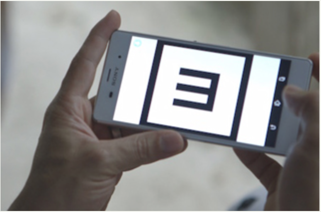 Image show hand holding a smartphone with a screen image from the vision screening application, a tumbling E letter sign.