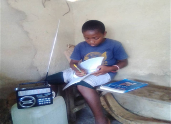 Liberian boy listens to the radio and takes notes in a workbook. Photo RTI International