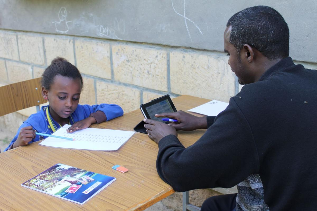 A child in Ethiopia participates in a reading assessment while an adult marks answers correct or incorrect.